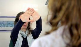 Mujer bonita joven experimentada una última prueba del estrabismo con el óptico del optometrista del oftalmólogo fotos de archivo libres de regalías