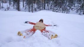 Mujer bonita joven feliz que lleva el traje divertido del tigre que miente en nieve acumulada por la ventisca en bosque del invie Imagenes de archivo
