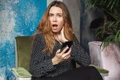 Mujer bonita joven hermosa emocional chocada que se sienta en café dentro usando la charla del teléfono móvil imagen de archivo