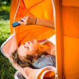Mujer bonita, joven que acampa al aire libre, mintiendo en la tienda Imagen de archivo libre de regalías
