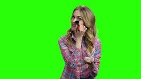 Mujer bonita joven que aplica maquillaje en la pantalla verde almacen de video
