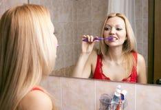 Mujer bonita joven que aplica sus dientes con brocha Imagen de archivo