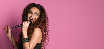 Mujer bonita joven que canta en cierre aislado micrófono para arriba imagen de archivo libre de regalías