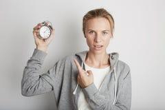 Mujer bonita joven que celebra el reloj de la alarma Backgroung blanco Fotos de archivo