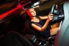 mujer bonita, joven que conduce su coche moderno en la noche, en una ciudad Imagen de archivo libre de regalías