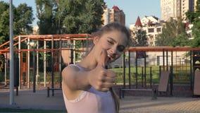 Mujer bonita joven que da los pulgares-para arriba a la cámara y que sonríe, gimnasio al aire libre en el fondo, feliz almacen de video