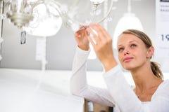 Mujer bonita, joven que elige la luz correcta para su apartamento Imagen de archivo