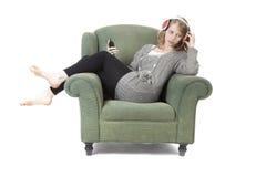 Mujer bonita joven que escucha la música en butaca Fotos de archivo libres de regalías