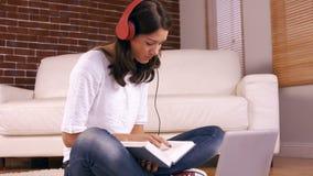 Mujer bonita joven que estudia en el piso metrajes