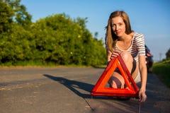 Mujer bonita, joven que fija el triángulo de la seguridad en el borde de la carretera fotos de archivo