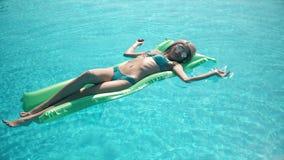 Mujer bonita joven que miente en el colchón de aire en la piscina almacen de metraje de vídeo