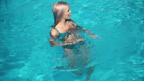 Mujer bonita joven que miente en el colchón de aire en la piscina almacen de video
