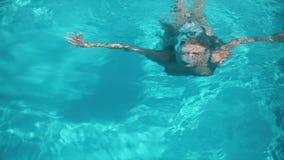 Mujer bonita joven que miente en el colchón de aire en la piscina metrajes