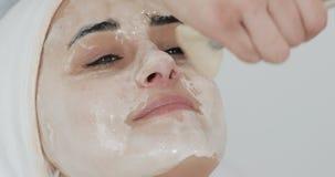 Mujer bonita joven que miente en el sofá en clínica de la cosmetología Ella que recibe la máscara facial blanca en salón de belle metrajes