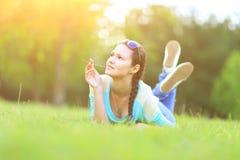 Mujer bonita joven que miente en hierba en la puesta del sol del verano Felicidad, diversión y armonía naturales Imagenes de archivo