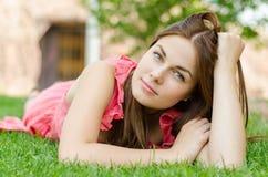 Mujer bonita joven que miente en hierba verde en parque Foto de archivo