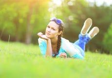 Mujer bonita joven que miente en la hierba en la puesta del sol del verano Fotografía de archivo