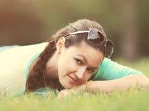 Mujer bonita joven que miente en la hierba en la puesta del sol del verano Felicidad natural, armonía de la diversión Fotos de archivo libres de regalías
