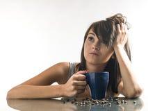 Mujer bonita, joven que mira las tazas de café en fondo brillante imagen de archivo