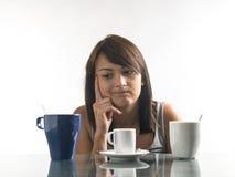 Mujer bonita, joven que mira las tazas de café en fondo brillante fotos de archivo