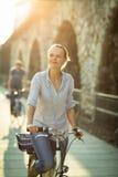 Mujer bonita, joven que monta una bicicleta en una ciudad Fotos de archivo