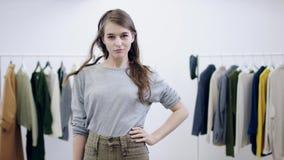 Mujer bonita joven que presenta delante de la cámara en un vestuario almacen de metraje de vídeo