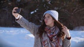 Mujer bonita joven que presenta para la cámara en el día de invierno soleado almacen de video