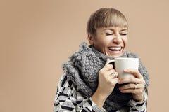 Mujer bonita joven que ríe con una taza blanca Fondo beige Imágenes de archivo libres de regalías