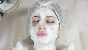 Mujer bonita joven que recibe tratamientos en salones de belleza Mujer de pelo oscuro hermosa joven en el cosmetólogo de la ofici almacen de metraje de vídeo
