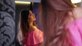 Mujer bonita joven que se admira en espejo en casa almacen de video