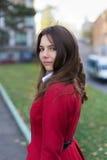 Mujer bonita joven que se coloca en el parque del otoño Imagen de archivo libre de regalías