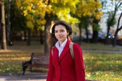 Mujer bonita joven que se coloca en el parque del otoño Foto de archivo libre de regalías