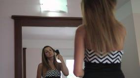 Mujer bonita joven que se peina el pelo antes de espejo en la cámara lenta interior blanca almacen de video