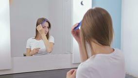 Mujer bonita joven que se peina el pelo delante del espejo almacen de metraje de vídeo