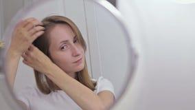 Mujer bonita joven que se peina el pelo delante del espejo almacen de video