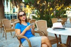 Mujer bonita joven que se relaja en el café al aire libre y que usa el smartp Fotografía de archivo libre de regalías
