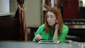 Mujer bonita joven que se sienta con vídeos o una animación, una tabla larga de la tableta y del reloj almacen de video