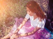 Mujer bonita joven que se sienta debajo del árbol Imágenes de archivo libres de regalías