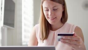 Mujer bonita joven que se sienta en casa El hacer compras en línea con la tarjeta de crédito en el ordenador portátil Consumerism almacen de metraje de vídeo