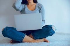 Mujer bonita joven que se sienta en el piso con el ordenador portátil Imagenes de archivo