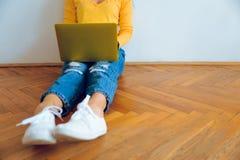Mujer bonita joven que se sienta en el piso con el ordenador portátil Foto de archivo