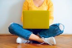 Mujer bonita joven que se sienta en el piso con el ordenador portátil Fotos de archivo libres de regalías