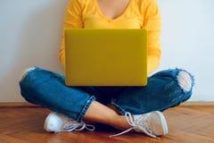 Mujer bonita joven que se sienta en el piso con el ordenador portátil Imagen de archivo