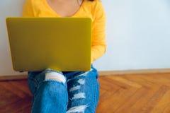 Mujer bonita joven que se sienta en el piso con el ordenador portátil Fotografía de archivo