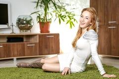 Mujer bonita joven que se sienta en la alfombra verde en su sala de estar Fotografía de archivo libre de regalías