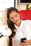 Mujer bonita joven que se sienta en tren usando móvil Imagenes de archivo