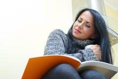 Mujer bonita joven que se sienta en un vector Foto de archivo
