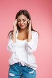 Mujer bonita joven que sufre del dolor de cabeza terrible que lleva a cabo la cabeza Foto de archivo libre de regalías