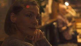 Mujer bonita joven que suspira tristemente, sentándose en el café, mirando a clientes, soledad metrajes