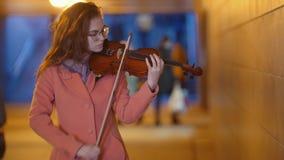 Mujer bonita joven que toca el violín en subterráneo metrajes